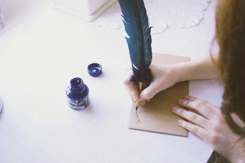 woman's hand addressing an envelope with quill pen