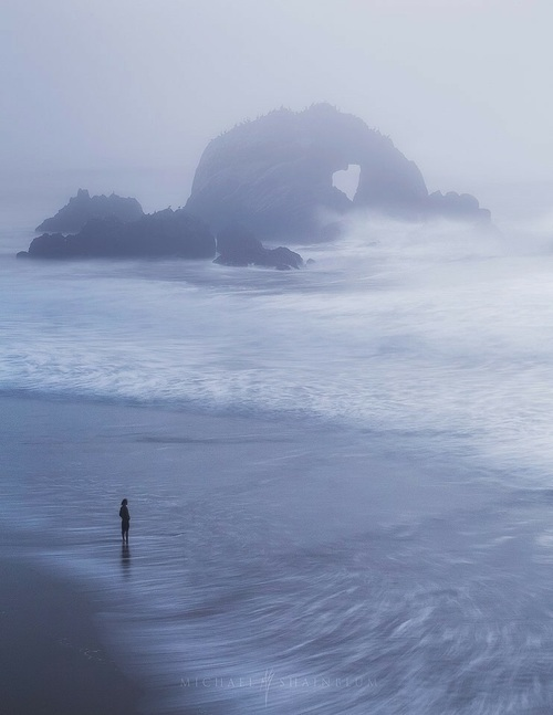 Woman beach rock formation in fog
