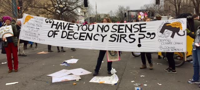 "Protesters holding sign that says ""Have you no sense of decency sirs?"""