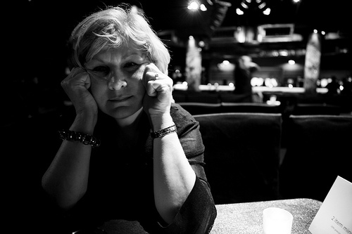 Black and white photo of older woman with grey hair with a sad expression