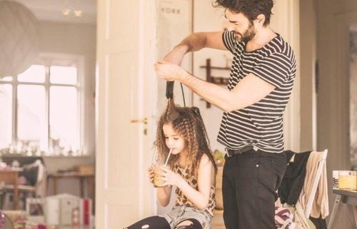 Father coparenting his daughter by tending to her hair.