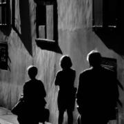 A family dealing with parental estrangement walking on a dark path alongside a building