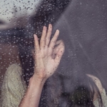 Woman's hand on a window thinking about why divorce hurts